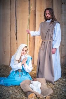 ベビーベッドで祈っている処女のメアリーとのキリスト降誕のシーンの垂直写真