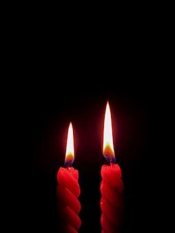 Вертикальная фотография пары красных свечей, горящих в темноте, со свободным пространством для текста или дизайна