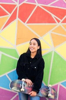 화려한 벽에 기대어 스케이트보드를 들고 웃고 있는 아시아 여성의 세로 사진