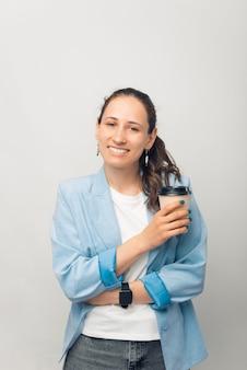 コーヒーブレイクをしている笑顔の女性の縦の写真。