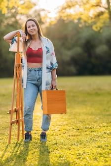 공원에서 나무 서류 가방과 캔버스를 들고 서 있는 여성의 세로 사진