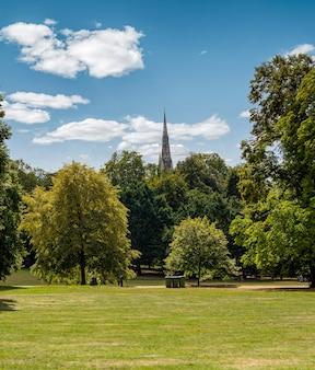 화창한 날에 백그라운드에서 떠오르는 교회의 끝으로 잔디와 나무가있는 도시 공원의 세로 사진