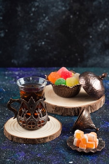 青い表面にカラフルなキャンディーと香りのよいお茶の垂直写真