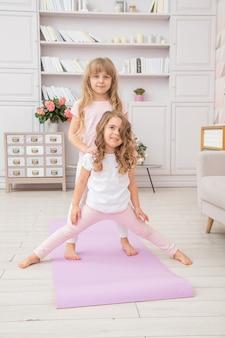 Вертикальное фото пары маленьких девочек играя на циновке йоги усмехаясь в живущей комнате, привычках здорового образа жизни и концепции образа жизни.