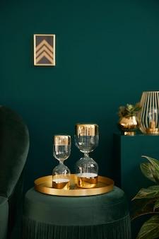 녹색 벨벳 푸프, 금 장식, 디자인 모래 시계, 벽에 액자 및 우아한 액세서리가있는 우아한 거실의 세로 사진. 아늑한 집에서 고급스러운 인테리어의 요소.
