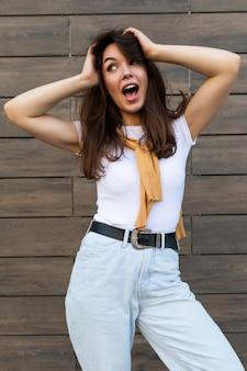 トレンディな衣装で感情的なポジティブな幸せな楽しいかなり若いブルネットの女性の垂直写真