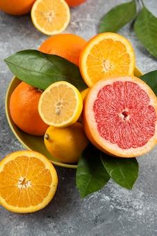 黄色いボウルに新鮮な柑橘系の果物の垂直写真。