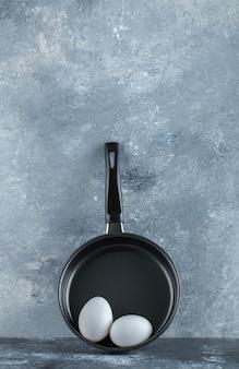 Вертикальное фото сковороды с яйцом.