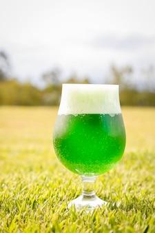잔디밭에 녹색 맥주 잔의 세로 사진. 성 패트릭의 날