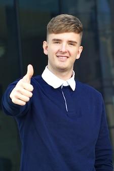 ジェスチャーや笑顔のように親指を上に表示するハンサムなポジティブな若い男の垂直写真
