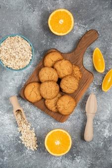 회색 테이블 위에 오트밀과 오렌지 조각이 있는 홈메이드 쿠키의 세로 사진.