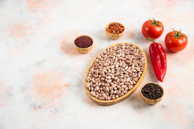さまざまな種類のスパイスとフレッシュトマトを添えた豆の山の縦の写真。