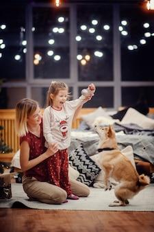 Вертикальное фото сидящей на полу счастливой светловолосой матери, держащей улыбающуюся дочь в пижаме, стоящей на ковре возле серой кровати, играющей с собакой сиба-ину перед большими ночными окнами