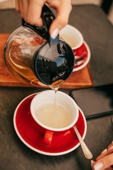 Вертикальное фото чайника и чашки на деревянном столе в руке женщины