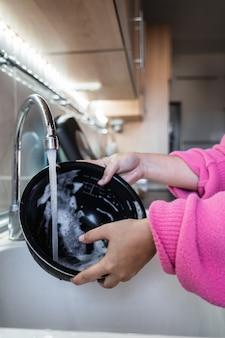 비누로 가득 찬 그릇에 물이 흐르는 소녀의 손의 세부 사항의 세로 사진