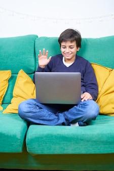 Вертикальное фото умного и жизнерадостного ребенка во время видеоконференции с ноутбуком, сидящего на диване у себя дома