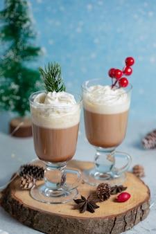 クリスマスの装飾が施された木の板に2つのボウルのアイスクリームの垂直写真。