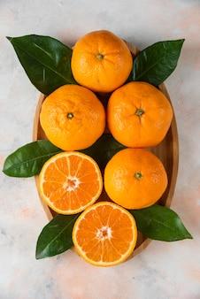 Вертикальное фото целых или половинных мандаринов клементина на деревянной тарелке. закрыть вверх