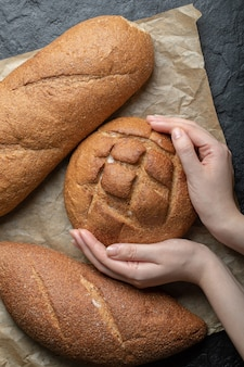 ライ麦パンを持っている女性の縦の写真。