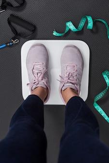 그녀의 진행 상황을 측정하기 위해 전기 규모에 여자의 다리의 세로 사진. 슬리밍 및 피트니스 생활의 개념.