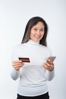 Вертикальное фото молодой счастливой женщины делая покупки онлайн с карточкой и smartphone