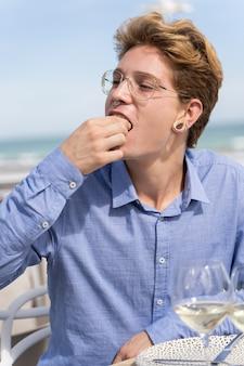 Вертикальное фото молодого человека с пирсингом и очки, едят суши еду своими руками с выражением удовольствия