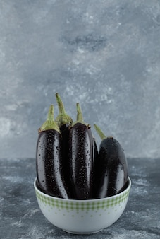 Vertical photo of pile of organic eggplants in bowl on grey background.