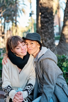 Vertical photo portrait of a mother and daughter together embracing and sitting on a bench in the city