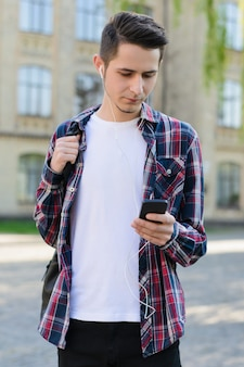手にガジェットデジタルデバイスを使用してインターネット上で新しいビデオを見ているハンサムな魅力的な集中スマート男の垂直写真の肖像画
