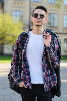 肩にジャケットを保持している自画像の誇り高きハンサムなマッチョな男の縦の写真の肖像画 Premium写真