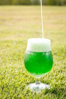 세로 사진, 잔디밭에 유리에 맥주를 넣어. 성 패트릭의 날.
