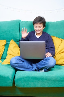 Vertical photo of the smart and cheerful child making a video conference with laptop sitting on the sofa at home