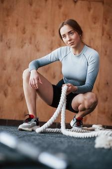 Вертикальное фото. спортивная молодая женщина имеет фитнес-день в тренажерном зале в утреннее время