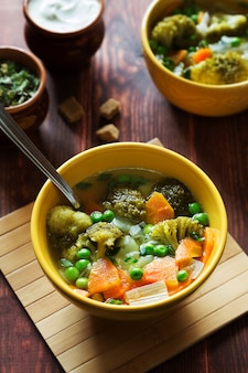 Vertical photo of vegetable soup with carrots, green peas and broccoli