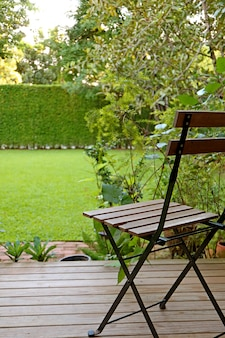 Vertical photo of vibrant green grass lawn backyard with a wooden chair for relaxing