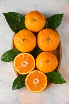 Vertical photo of whole or half cut clementine mandarins over wooden plate. close up