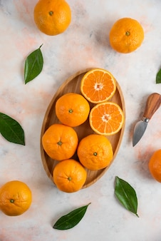 Vertical photo of whole or half cut clementine mandarins over wooden plate