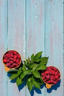あなたのテキストのための場所、水色の木製の背景の上のカップに熟したラズベリーの縦の写真。自然の中で素朴なスタイルの朝食の明るい夏のコンセプト。