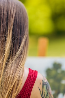 공원에서 페인트 칠한 캔버스 앞에 있는 여성의 등에 선택적 초점이 있는 세로 사진