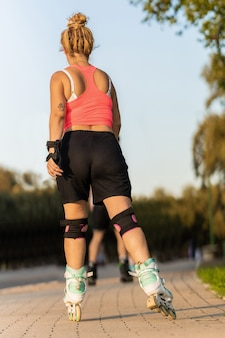Vertical photo of a woman in her back skating with inline skate