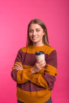 Vertical photo of a woman smiling at the camera while holding a to go coffee cup.