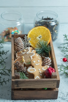 Foto verticale della scatola di legno piena di snack. biscotti fatti in casa e fetta d'arancia con pigne.