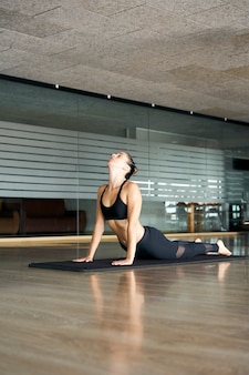 Vertical photo of a young woman practicing yoga or pilates in a gym, exercising in black sportswear, doing back extension. bhujangasana