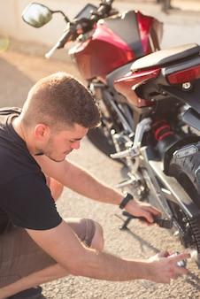 오토바이의 적절한 기능을 위해 유지 보수를 수행하는 어린 소년의 세로 사진, 청소 및 기름칠