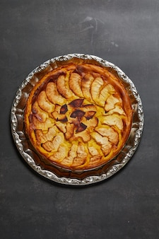 Vertical picture of an apple cake on a grey surface