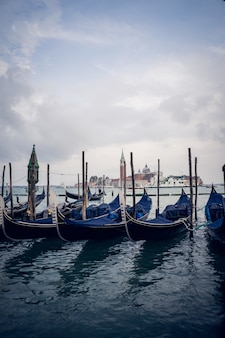 Vertical picture of blue gondolas in a port at daytime