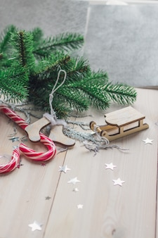 Vertical picture of candy canes and christmas decorations on a wooden table under the lights