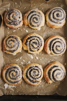 Vertical picture of delicious poppy snail pastries with a sugar glaze in a tray on wooden table