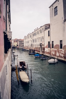 Vertical picture of gondolas on the grand channel between colorful buildings in venice, italy