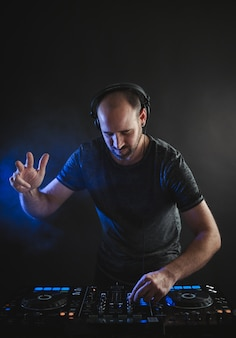 Vertical picture of a male dj working under the blue lights in a studio